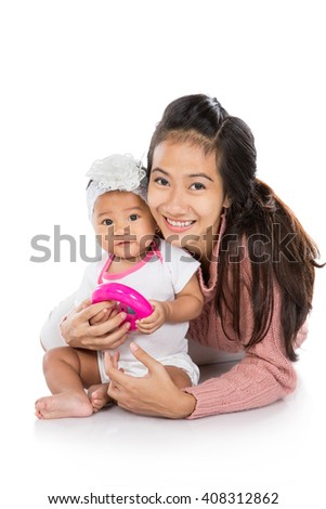 attractive mother holding her baby girl while sitting on a floor - stock photo