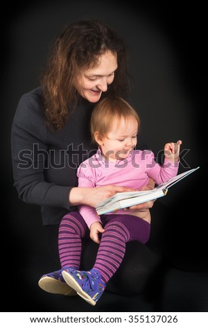 Attractive mother shows pictures in book to her cute little 15 monthes old daughter over black background - stock photo