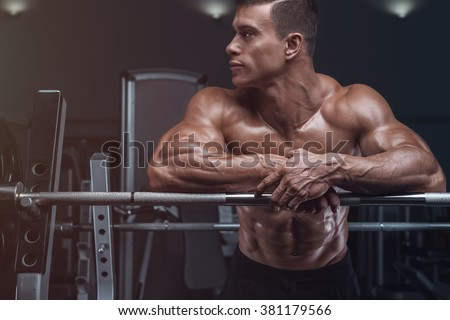 Attractive muscular bodybuilder guy prepare to do exercises with barbell in a gym - stock photo