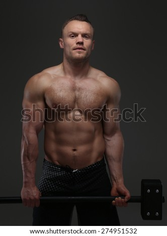 Attractive muscular guy holding hummer. Studio shoot. Isolated on grey background - stock photo