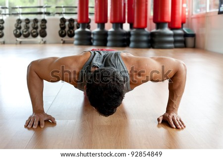Attractive muscular man doing push-ups on a wooden floor. - stock photo