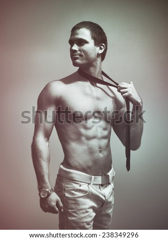 Attractive muscular man posing with tie. Black and white. filter - stock photo