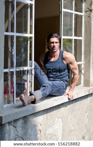 Attractive, muscular man sitting on open window looking in camera, wearing dark tanktop - stock photo