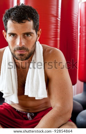 Attractive muscular sports man with a towel on his shoulders sitting down and looking tired. Fighter. - stock photo
