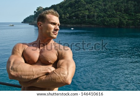 Attractive muscular young man with arms crossed and sea or ocean behind, large copyspace - stock photo