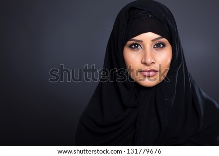 attractive Muslim woman on black background - stock photo
