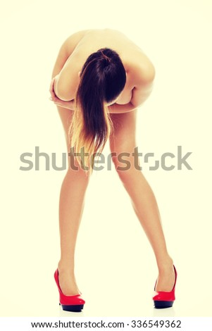 Attractive naked fashion model wearing only red high heels. - stock photo
