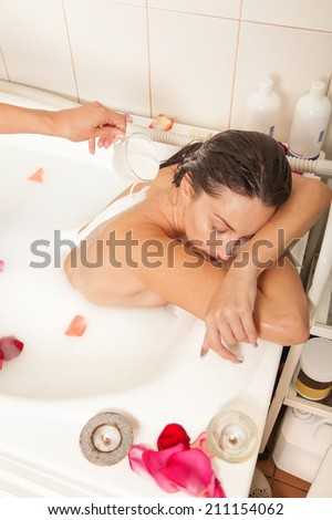 Attractive naked girl enjoys a bath with milk and rose petals.Spa treatment for skin nutrition and moisturizing skin renewal - stock photo