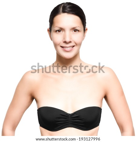 Attractive naked slim young woman wearing a black strapless bra standing looking directly at the camera with a smile, isolated on white - stock photo