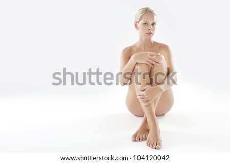 Attractive naked woman isolated on a white background, looking at camera. - stock photo