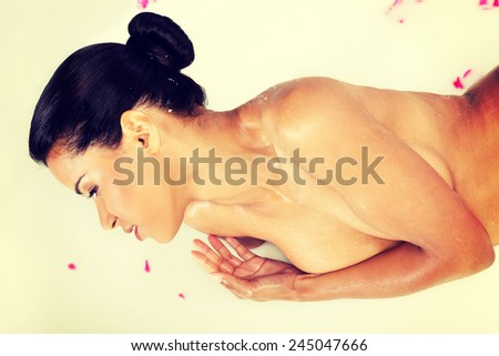Attractive naked woman lying in a milk-bath with rose petal.