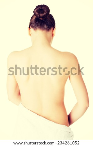 Attractive naked woman's back covered with towel. Isolated on white. - stock photo