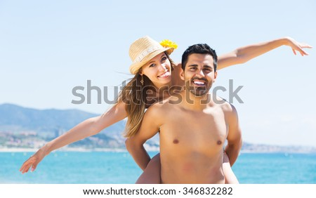 Attractive newly married couple having homeymoon at tropical beach - stock photo