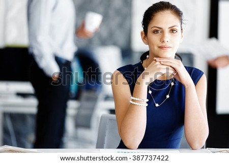 Attractive office worker sitting at desk - stock photo