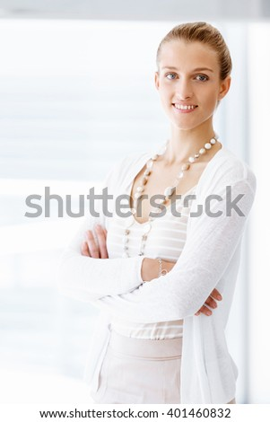 Attractive office worker standing next to window - stock photo