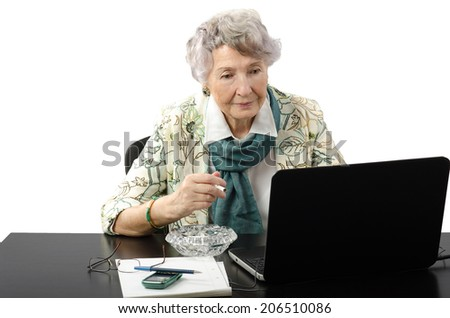 Attractive old business woman stares at the laptop screen - stock photo