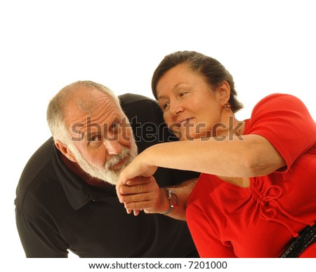 Attractive older couple in love with the gentleman kissing his lovely dame's hand; isolated on white - stock photo