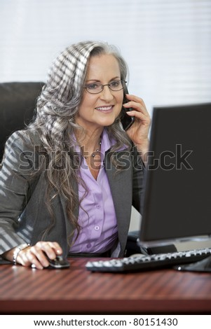 Attractive older woman working and talking on phone. - stock photo