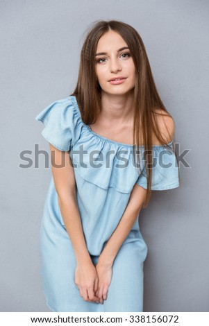 Attractive pensive young pretty woman with long hair in blue dress posing on gray background - stock photo