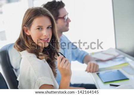 Attractive photo editor biting her reading glasses next to a colleague