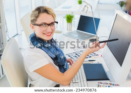Attractive photo editor pointing at the screen in office - stock photo