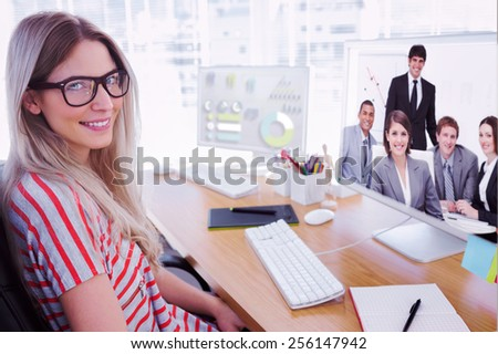Attractive photo editor working on computer against happy business group having a meeting - stock photo