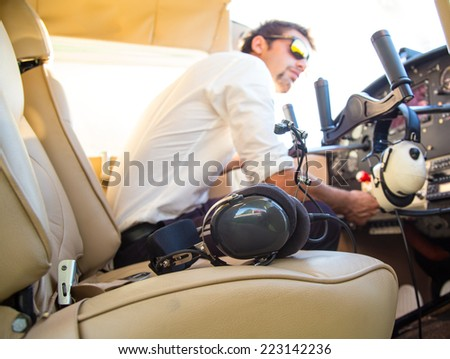 attractive pilot sitting in the plane - stock photo