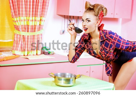 Attractive pin-up girl cooking on her pink kitchen. Retro style. Fashion. - stock photo