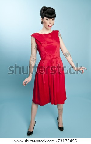 Attractive pinup model wearing red dress - stock photo