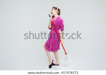 Attractive playful young housewife singing and dancing with mop  - stock photo