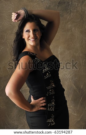 Attractive plus-sized fashion model posing in dark party dress in studio setting. - stock photo