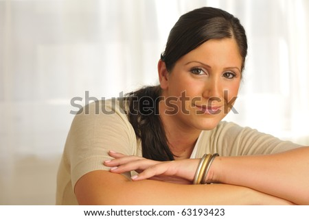 Attractive plus-sized model relaxing in bright room. - stock photo