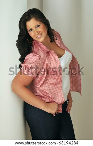 Attractive plus-sized model wearing red blouse in studio setting. - stock photo