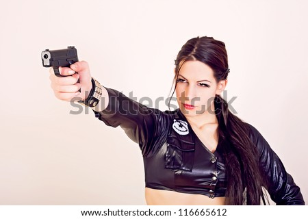 Attractive police woman holding a gun - stock photo