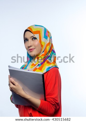 Attractive portrait of young muslim woman holding books, while thinking and smiles