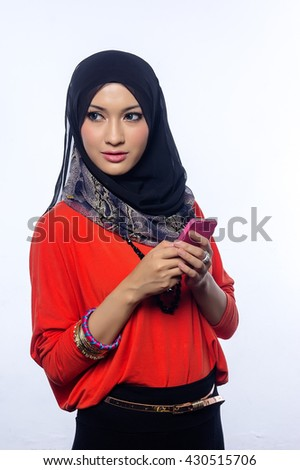 Attractive portrait of young muslim woman holding mobilephone - stock photo