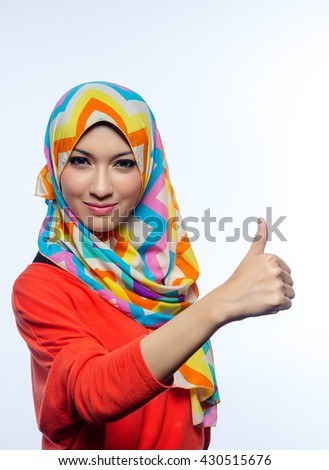 Attractive portrait of young muslim woman with thumb up - stock photo