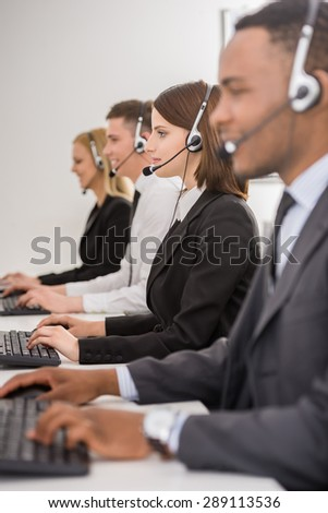 Attractive positive young colleagues working in call center office. Side view.