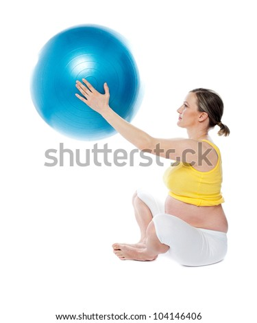 Attractive pregnant lady practicing yoga with gymnastic ball isolated over white