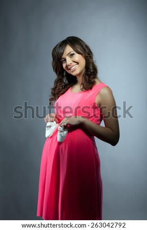 Attractive pregnant woman posing in elegant dress - stock photo