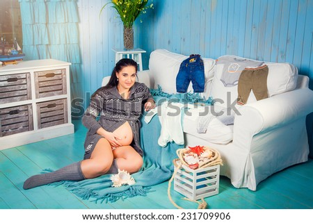 Attractive pregnant woman touching her belly and sitting near the couch - stock photo