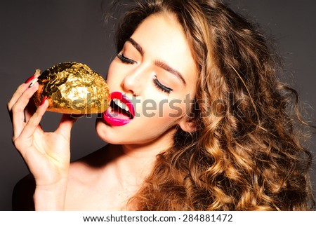 Attractive pretty young girl with curly hair and bright pink lips holding golden bread roll near face standing with closed eyes and open mouth on dark grey background, horizontal picture
