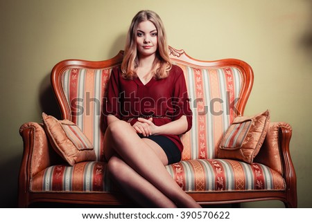 Attractive pretty young woman sitting on vintage retro sofa couch. Elegant fashionable gorgeous girl wearing maroon shirt and skirt. Fashion. - stock photo