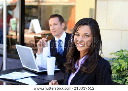 Attractive Professional Business Man and Woman Working On A Group Project in Front of A Computer and Drinking Coffee