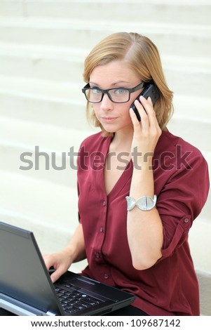 Attractive Professional Business Woman Frustrated, On the Phone and computer, and Looking to the Camera - stock photo