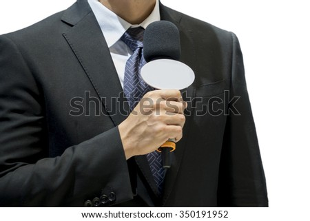 Attractive professional male news reporter holding microphone, talking to camera live broadcasting. - stock photo