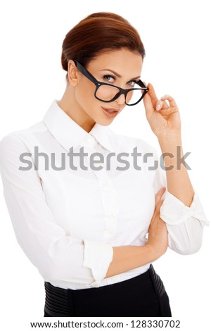 Attractive professional woman standing peering over the top of the frames of her glasses at the camera isolated on white