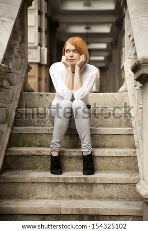 attractive rad-haired lady sitting on stairs of old building - stock photo