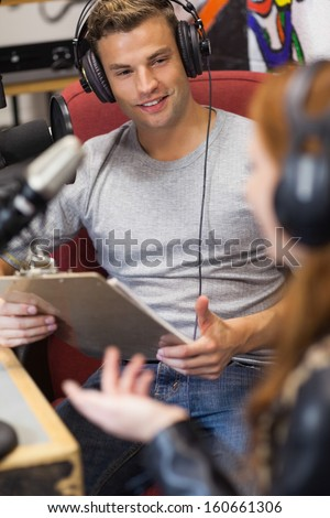 Attractive radio host interviewing a guest holding clipboard in studio at college - stock photo
