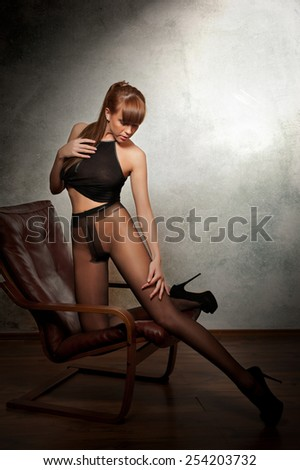 Attractive red hair model with black pantyhose sitting provocatively on armchair - gray background. Portrait of a sensual woman - studio shot. Beautiful redhead female in black posing provocatively.